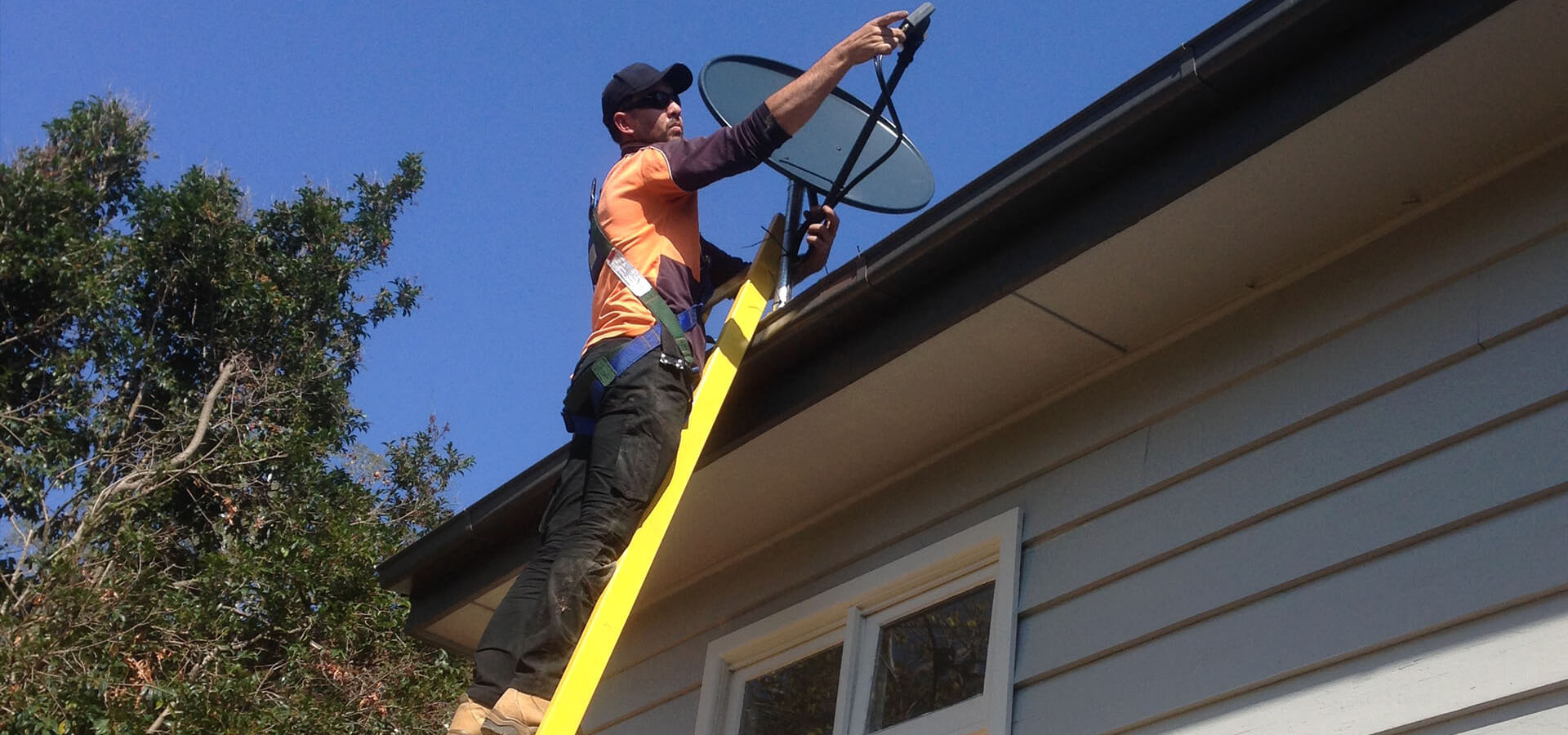 Installer using the Branach fibreglass CorrosionMaster Single Ladder to climb on a roof.