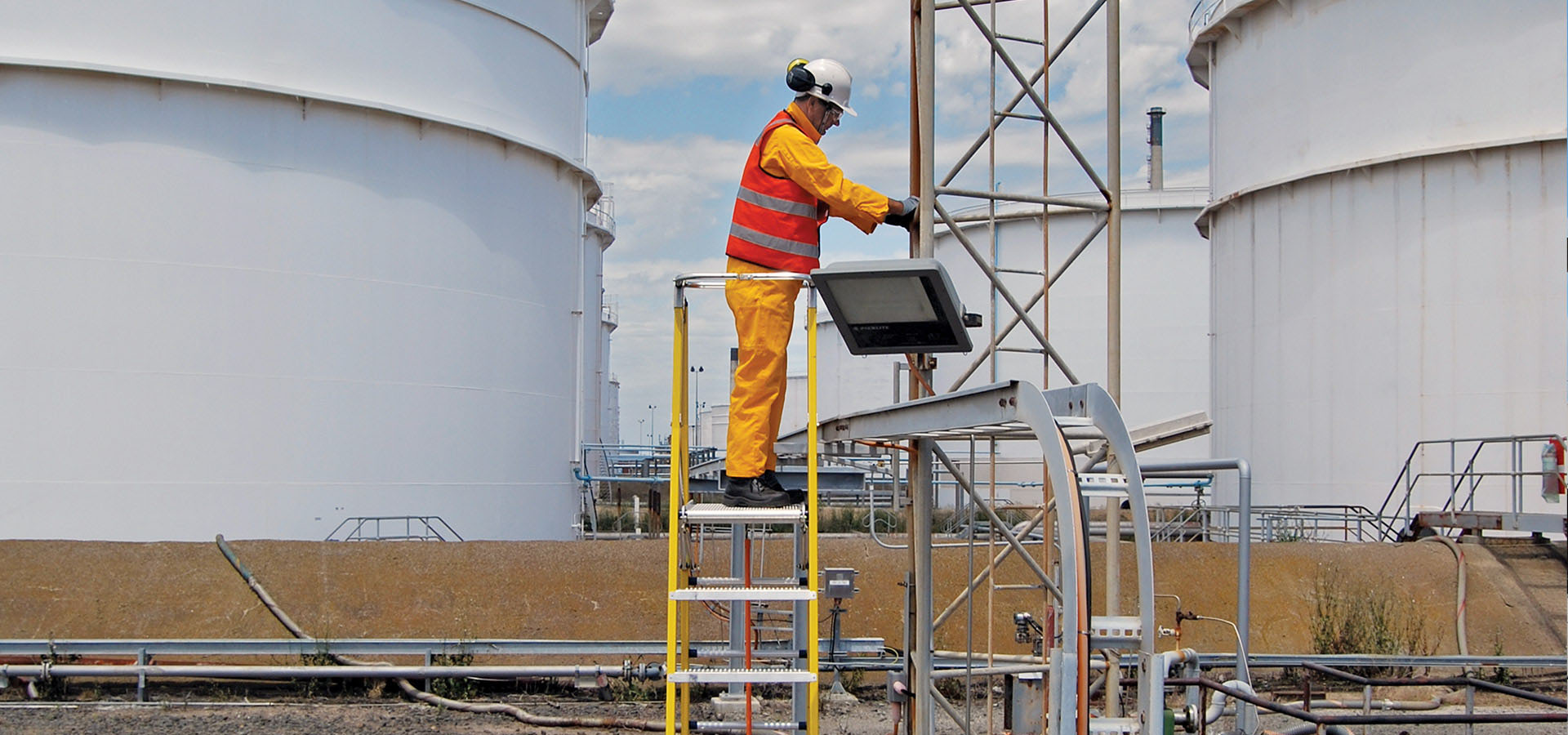 A refinery worker standing on the Branach fibreglass WorkMaster 450mm Step Platform Ladder.